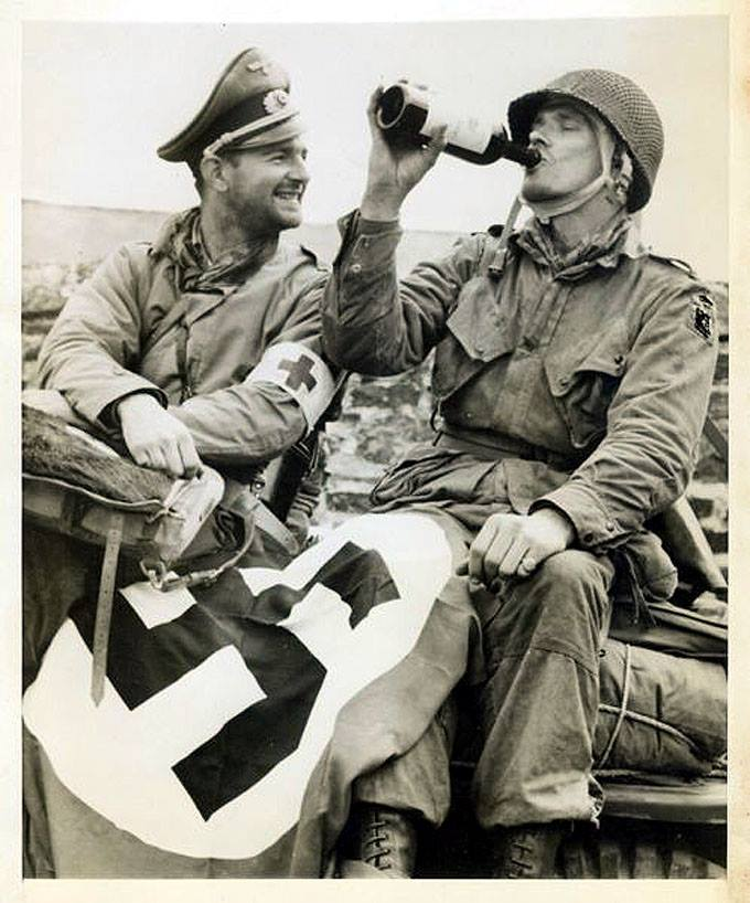 A rescued member of the 82nd Airborne captured during the D-Day drops drinks some 'liberated' wine while a medic with captured German items enjoys the levity of the moment. France 1944.jpg